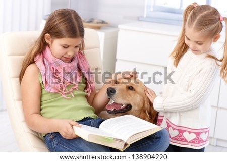 Schoolgirl studying at home while stroking golden retriever with sister, smiling.