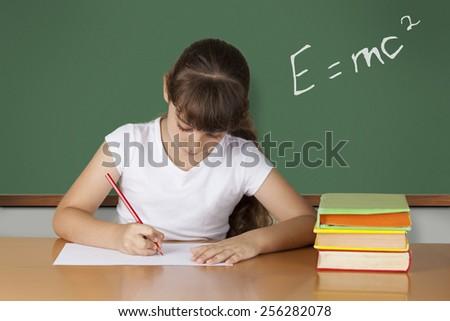 Schoolgirl studying at the classroom - stock photo