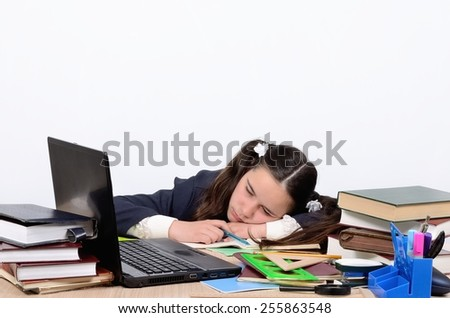 Schoolgirl teen tired of training and slept with his head on school desk near the computer - stock photo