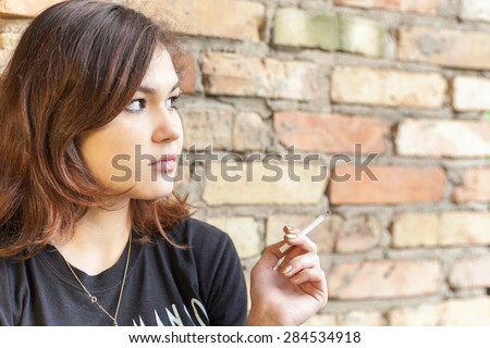 Schoolgirl teenager smokes outdoor on brick wall background. Smoking is harmful to our health - stock photo