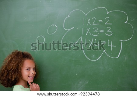 Schoolgirl thinking about mathematics in front of a blackboard - stock photo