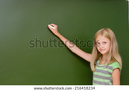 Schoolgirl wants to write something on the blackboard
