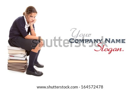 Schoolgirl with a bored look sitting on a pile of books - stock photo