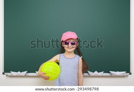Schoolgirl with ball near the school board - stock photo