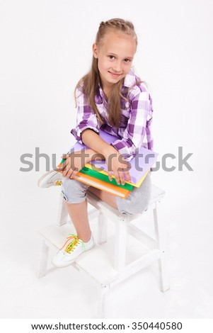 schoolgirl with books in their hands and sitting on a chair on a white background and looking at the camera.