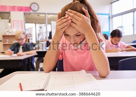 Schoolgirl with head in hands in an elementary school class - stock photo