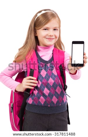 Schoolgirl with mobile phone in hand looking at the camera and smiling, picture with depth of field and artistic blur - stock photo
