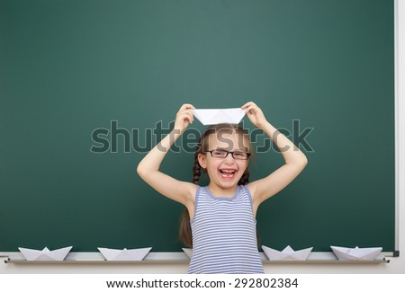Schoolgirl with origami ship near the school board - stock photo