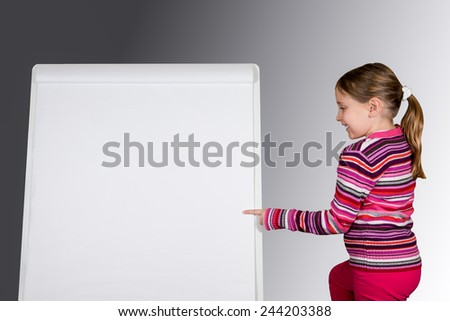 Schoolgirl with ponytail pointing at message board.  Enter your text.  Smiling and looking at flip chart.  Isolated studio shot.