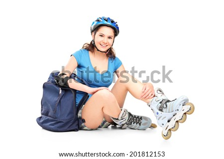 Schoolgirl with roller skates sitting on the ground isolated on white background
