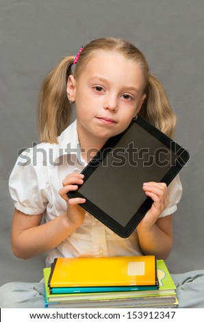 Schoolgirl with the tablet and notebooks. Portrait