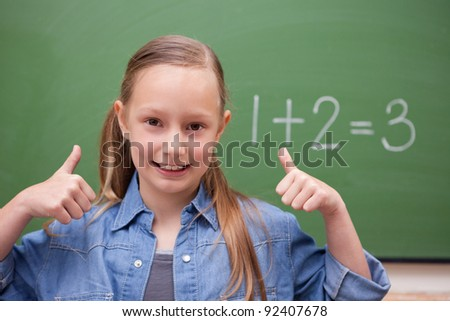 Schoolgirl with the thumbs up in front of a backboard - stock photo