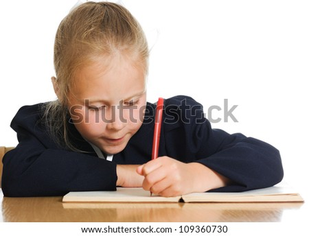 Schoolgirl writes at a table on a white background. - stock photo