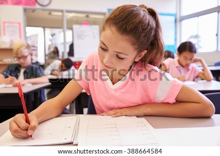 Schoolgirl writing at her desk in an elementary school class - stock photo