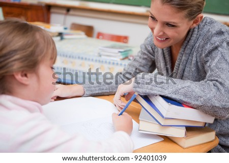 Schoolgirl writing with her smiling teacher in a classroom - stock photo