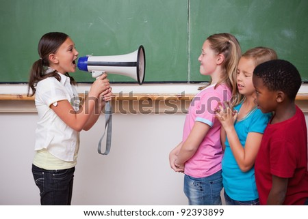 Schoolgirl yelling through a megaphone to her classmates in a classroom - stock photo