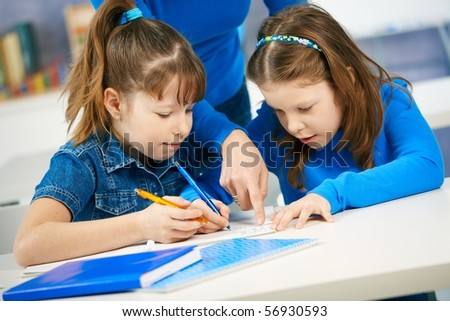 Schoolgirls learning together in primary school classroom. Elementary age children.? - stock photo