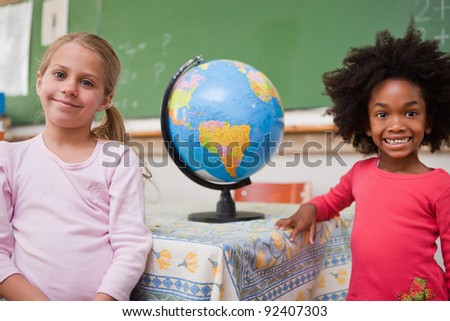 Schoolgirls posing with a globe in a classroom