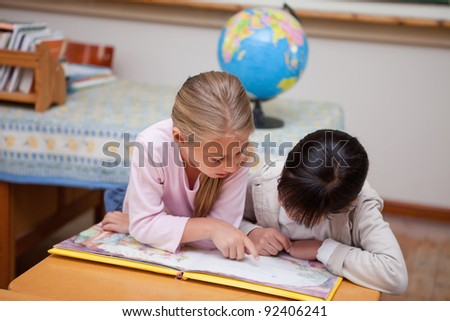 Schoolgirls reading a fairy tale in a classroom