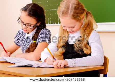 Schoolgirls sit at their desk during a lesson. Education.