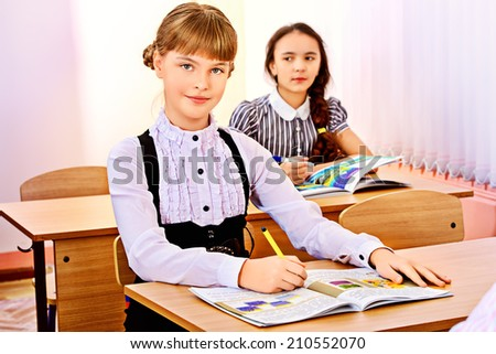 Schoolgirls sit at their desks during a lesson. Education.