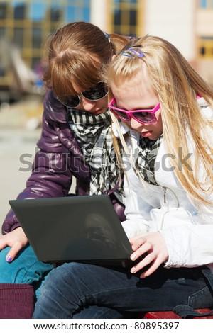 Schoolgirls working on laptop - stock photo