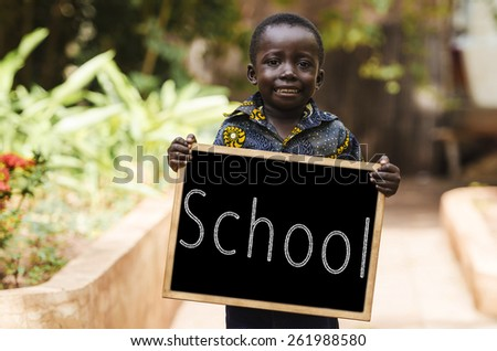 Schooling Symbol - African Little Boy with Blackboard. African boy holding a chalkboard in the streets of Bamako. - stock photo