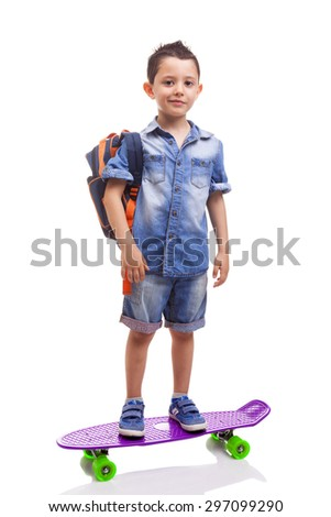 Schoolkid standing with a skateboard and backpack on white background - stock photo