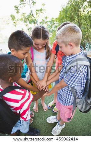 Schoolkids putting their hands together in campus at school