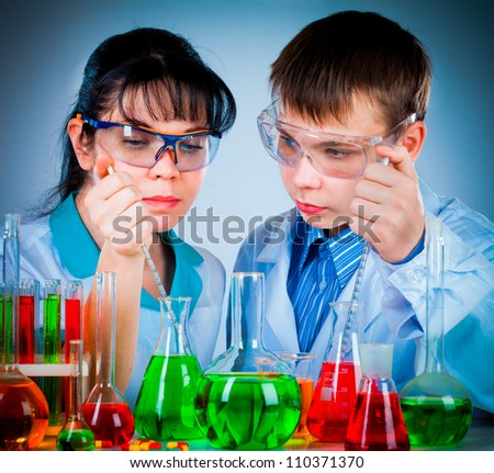 schoolteacher and student working in the lab - stock photo