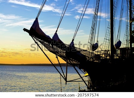 Schooner Sunrise. Silhouette of the bow of a tall ship set against a sunrise sky.  - stock photo