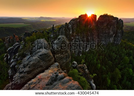 Schrammsteine, beautiful evening view over sandstone cliff into deep misty valley in Saxony Switzerland, foggy background, the fog is orange due to sunset, star sun on sky, Germany - stock photo