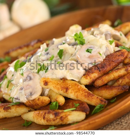 Schupfnudeln (Swabian potato noodles from Southern Germany) with mushroom sauce (Selective Focus, Focus on the front of the mushroom sauce)