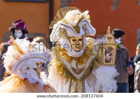 SCHWAEBISCH-HALL, GERMANY - February 23, 2014 - A couple, dressed up in a Venetian style costume with golden masks attend the Hallia Venetia Carnival festival on February 23, 2014 in Schwaebisch-Hall. - stock photo