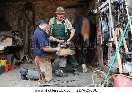 Schwarzhofen, Bavaria - September 02, 2014. Blacksmith, or equine farrier with the  horse owner at work while changing a horseshoe, before the start of autumn seasonal work