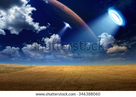 Sci-fi background - alien spaceship shines spotlight on wheat field, aliens invasion, star wars. Elements of this image furnished by NASA nasa.gov - stock photo