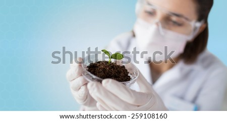 science, biology, ecology, research and people concept - close up of young female scientist wearing protective mask holding petri dish with plant and soil sample over blue background - stock photo
