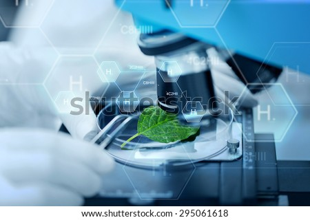 science, chemistry, biology and people concept - close up of scientist hand with microscope and green leaf making research in clinical laboratory over hydrogen chemical formula - stock photo