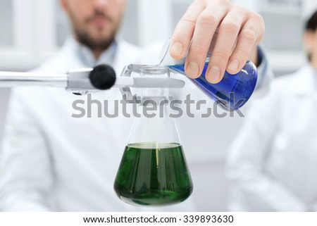 science, chemistry, biology, medicine and people concept - close up of scientist hand filling test tubes and making research in clinical laboratory - stock photo