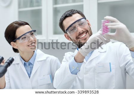 science, chemistry, biology, pharmacy and people concept - young scientists with pipette and flask making test or research in clinical laboratory - stock photo