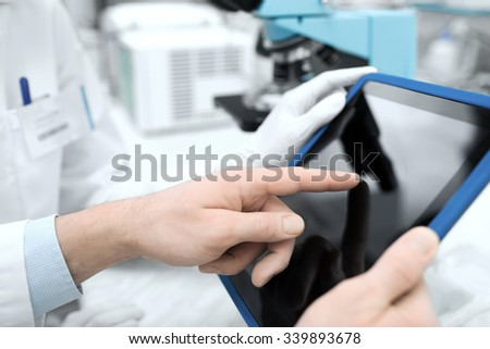science, chemistry, technology, biology and people concept - close up of scientists hands with tablet pc in lab - stock photo