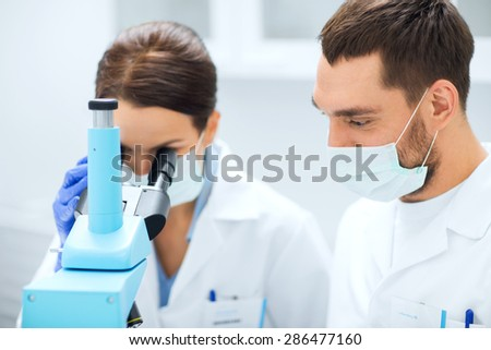 science, chemistry, technology, biology and people concept - young scientists in masks looking to microscope and making test or research in clinical laboratory - stock photo