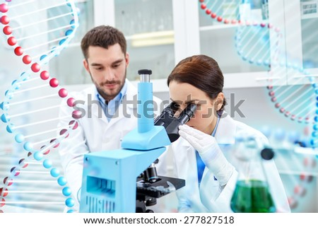 science, chemistry, technology, biology and people concept - young scientists looking to sample through microscope and making test or research in clinical laboratory over dna molecule structure - stock photo
