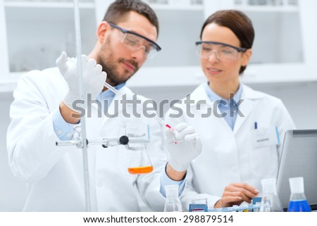 science, chemistry, technology, biology and people concept - young scientists with pipette and glass making test or research in clinical laboratory - stock photo