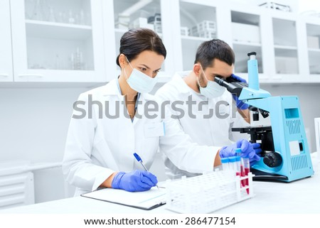 science, chemistry, technology, biology and people concept - young scientists with test tube and microscope making research in clinical laboratory and taking notes - stock photo