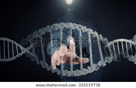 Science concept image of human hand touching DNA molecule - stock photo