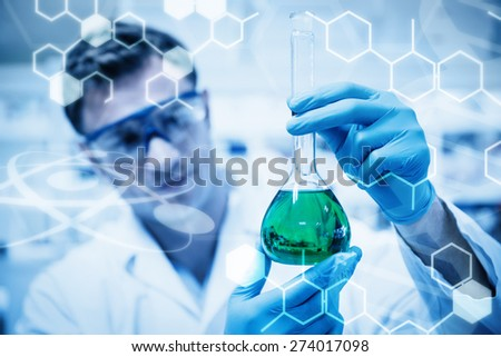Science graphic against chemist holding up beaker of green chemical - stock photo