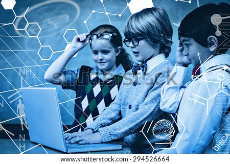 Science graphic against school kids using laptop in classroom - stock photo