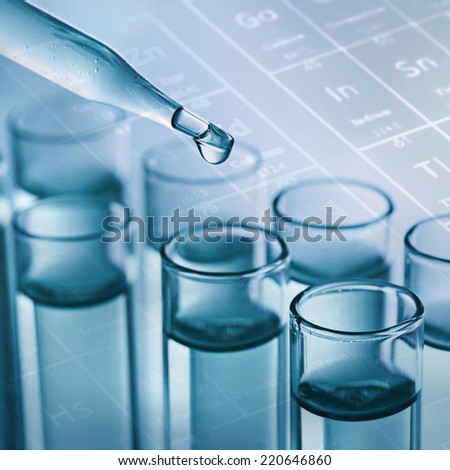 science laboratory test tubes with periodic table background - stock photo