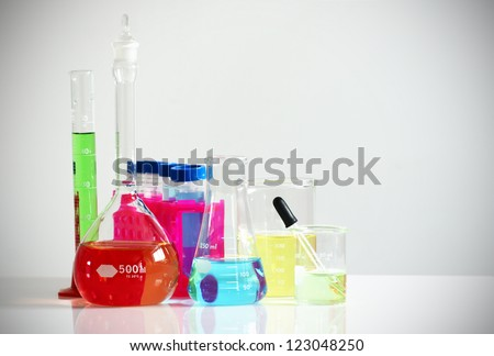 Science, research or chemistry concept: set of different laboratory glassware, flask, beaker and others filled with colorful chemicals or liquids. - stock photo